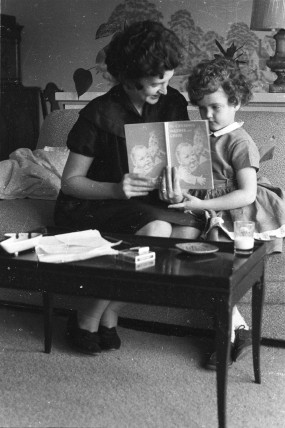 A woman reading to a child.