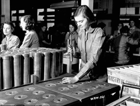 Woman uses hammer to tap 25-pounder field gun case at a munitions plant (prob. Robert Mitchell Co.)