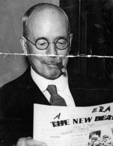 Man in glasses with cigar reading a newspaper.